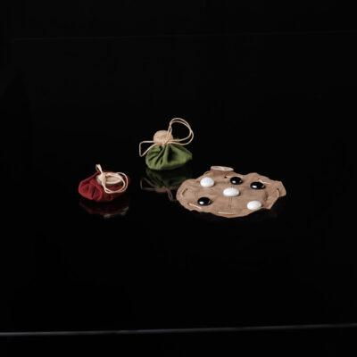 Eine Spielfläche aus braunem, rotem oder grünem Kunstleder, zweimal 3 Glassteine und ein Vielfaches an Spaß!