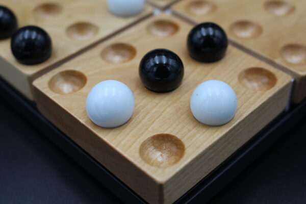 Detailansicht auf Spielbrett aus Holz und Glaskugeln – für alle, die ein ausgefallenes Geschenk suchen!